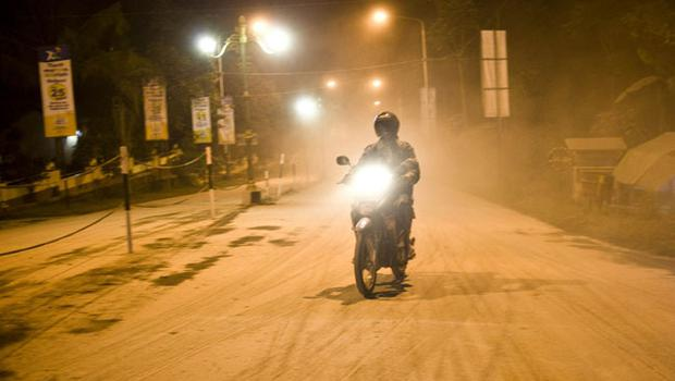 YOGYAKARTA, INDONESIA - OCTOBER 26:  A motorcycle rides up a street, blanketed in ash from the erupting Mount Merapi volcano, at Kaliurang village in Sleman, on October 26, 2010 near  Yogyakarta, Indonesia. Thousands have been ordered to evacuate as Mount Merapi, which last erupted in 2006, began to emit plumes of smoke and clouds of ash. (Photo by Ulet Ifansasti/Getty Images)