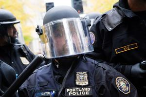 PORTLAND - NOVEMBER 13: A police man in riot gear watches as protesters continue to chant slogans and sing songs near the Occupy Portland encampment November 13, 2011 in Portland, Oregon. Portland police have reclaimed the two parks in which occupiers have been camping after a night of brinksmanship with protesting crowds of several thousands. (Photo by Natalie Behring/Getty Images)