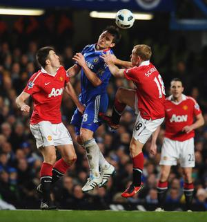 LONDON, ENGLAND - MARCH 01: Frank Lampard of Chelsea wins a header against Michael Carrick (L) and Paul Scholes of Manchester United during the Barclays Premier League match between Chelsea and Manchester United at Stamford Bridge on March 1, 2011 in London, England.  (Photo by Clive Mason/Getty Images)
