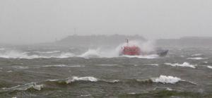 Waves break over a pilot boat returning to Portsmouth as fierce storms battered Britain today, with heavy rain and winds gusting up to 85mph