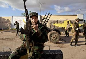 A Libyan soldier from forces that  defected against Libyan leader Moammar Gadhafi guards next to an anti-aircraft battery outside a military base in Benghazi, eastern Libya, Monday, Feb. 28, 2011. (AP Photo/Kevin Frayer)