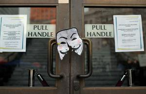 OAKLAND, CA - NOVEMBER 12:  A paper Guy Fawkes mask is posted on the doors of Oakland City Hall across from the Occupy Oakland encampment on November 12, 2011 in Oakland, California.  In the wake of violent confrontations with police, vandalism and the recent shooting near the encampment, Oakland mayor Jean Quan and city administrators have issued eviction notices to protesters at the Occupy Oakland encampment and have asked them to leave immediately.  (Photo by Justin Sullivan/Getty Images)
