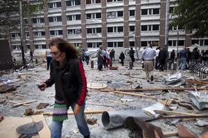 A woman walks through debris in a street following an explosion in Oslo, Norway Friday July 22, 2011. A powerful blast tore open several Oslo buildings including the prime minister's office on Friday