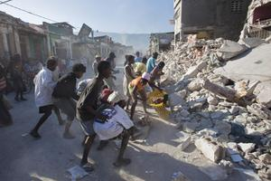 People fight over goods scavenged from the rubble of buildings collapsed during Tuesday's earthquake  in Port-au-Princeac