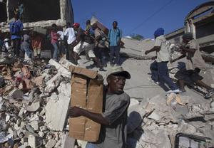 Scavengers look for goods amid the rubble