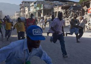People, carrying scavenged goods, run away from the police in Port-au-Prince, Friday, Jan. 15, 2010