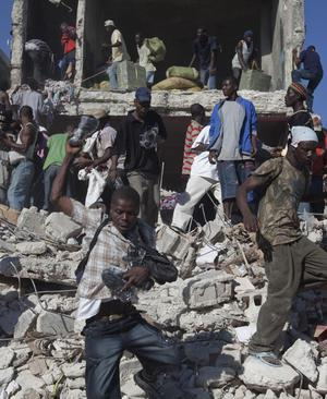 Scavengers look for goods amid the rubble of collapsed buildings in Port-au-Prince, Friday, Jan. 15, 2010