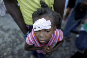 An injured child waits for medical attention in front of a damaged hospital in Carrefour, in the outskirts of Port-au-Prince