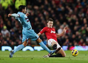 MANCHESTER, ENGLAND - NOVEMBER 28:  Michael Carrick of Manchester United tackles James Tomkins of West Ham United during the Barclays Premier League match between Manchester United and West Ham United at Old Trafford on November 28, 2012 in Manchester, England.  (Photo by Clive Brunskill/Getty Images)