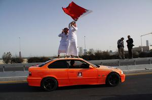 MANAMA, BAHRAIN - FEBRUARY 18:  Pro-government demonstrators ride atop a car during a show of support for the monarchy on February 18, 2011 in Manama, Bahrain. Anti-government protesters were fired at with live ammunitions, with protesters saying it was followed by teargas, which drove the demonstrators back. There are unconfirmed reports that there are four dead in the clashes.  (Photo by John Moore/Getty Images)