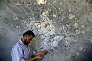 A Syrian man holds bullets he picked from a wall in a damaged house in town of Atareb outskirts of Aleppo, Syria. (AP Photo)