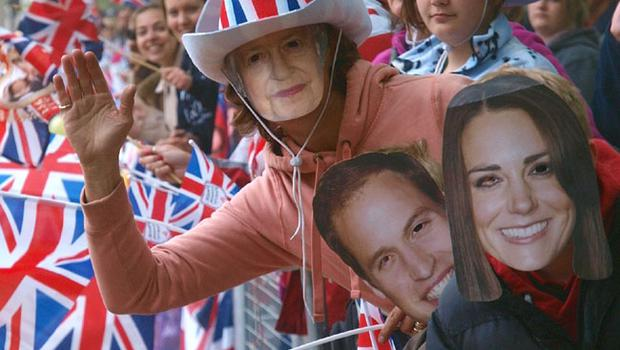 LONDON, ENGLAND - APRIL 29:  Royal fans wearing a  Kate Middleton mask, right, a Prince William mask, 2nd right, and a Queen Elizabeth mask ahead of the Royal Wedding of Prince William to Catherine Middleton at Westminster Abbey on April 29, 2011 in London, England. The marriage of the second in line to the British throne is to be led by the Archbishop of Canterbury and will be attended by 1900 guests, including foreign Royal family members and heads of state. Thousands of well-wishers from around the world have also flocked to London to witness the spectacle and pageantry of the Royal Wedding. (Photo by Max Nash - WPA Pool/Getty Images)