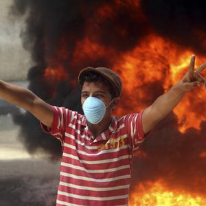 A protester wears a mask as he gestures during clashes with security forces in Cairo, Egypt (AP)