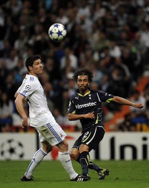 MADRID, SPAIN - APRIL 05:  Benoit Assou-Ekotto of Tottenham Hotspur (R) makes a pass under a challenge by Xabi Alonso of Real Madrid during the UEFA Champions League quarter final first leg match between Real Madrid and Tottenham Hotspur at Estadio Santiago Bernabeu on April 5, 2011 in Madrid, Spain. Real Madrid won 4-0.  (Photo by David Ramos/Getty Images)