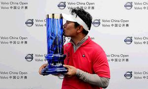 Y.E Yang kisses his trophy after winning the Volvo China Open in Suzhou yesterday.
