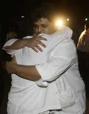 ** ALTERNATE CROP ** Employees of The Taj Hotel comfort each other after they were rescued from the hotel in Mumbai, India, Thursday, Nov. 27, 2008. (AP Photo/Gautam Singh)
