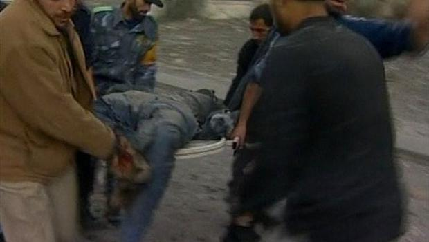 In this image taken from APTN video young men carry a badly injured man on a stretcher to an awaiting vehicle after Israeli aircraft struck Hamas security compounds across Gaza in Gaza City on Saturday Dec. 27, 2008. Hamas and medics reported that dozens of people were killed and that others were still buried under the rubble. The strikes caused widespread panic and confusion, as black clouds of smoke rose above Gaza. (AP Photo/APTN)