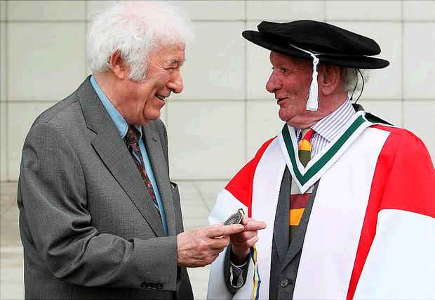 Playwright Brian Friel shows his University College Dublin Ulysses Medal to Seamus Heaney