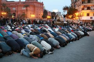 CAIRO, EGYPT - JANUARY 30:  People pray in front of army tanks in Tahrir Square on January 30, 2011 in Cairo, Egypt. Cairo remained in a state of flux and marchers continued to protest in the streets and defy curfew, demanding the resignation of Egyptian president Hosni Mubarek. As President Mubarak struggles to regain control after five days of protests he has appointed Omar Suleiman as vice-president. The present death toll stands at 100 and up to 2,000 people are thought to have been injured during the clashes which started last Tuesday. Overnight it was reported that thousands of inmates from the Wadi Naturn prison had escaped and that Egyptians were forming vigilante groups in order to protect their homes.   (Photo by Peter Macdiarmid/Getty Images)