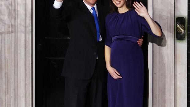 Britain's new Prime Minister David Cameron and his wife, Samantha, wave on the doorstep of 10 Downing Street