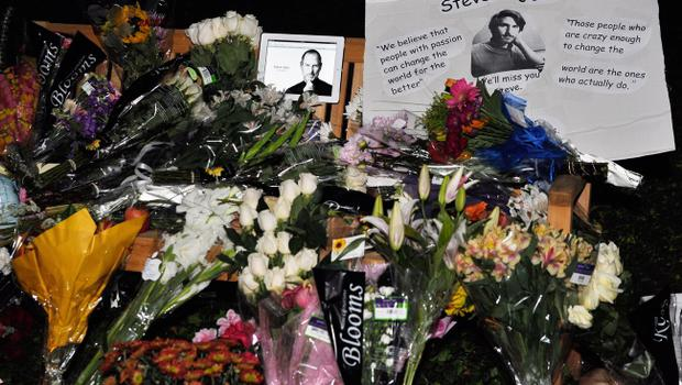 CUPERTINO, CA - OCTOBER 05:  Flowers and an iPad showing a picture of Steve Jobs are placed at a makeshift memorial for Steve Jobs at the Apple headquarters on October 5, 2011 in Cupertino, California. Jobs, 56, passed away after a long battle with pancreatic cancer. Jobs co-founded Apple in 1976 and is credited, along with Steve Wozniak, with marketing the world's first personal computer in addition to the popular iPod, iPhone and iPad.  (Photo by Kevork Djansezian/Getty Images)