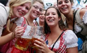 MUNICH, GERMANY - SEPTEMBER 23:  Revellers, dressed with traditional Bavarian clothes celebrate at Schottenhamel beer tent during day 2 of Oktoberfest beer festival on September 22, 2012 in Munich, Germany.This year's edition of the world's biggest beer festival Oktoberfest will run until October 7, 2012.  (Photo by Johannes Simon/Getty Images)