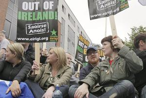 Protestors make their way down a street in Dublin after the Queen arrived in the country for a four day state visit.