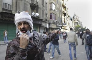 Egyptian protesters shouts at the scene of a building fire, seen in background, near Tahrir Square in Cairo, Egypt, Monday, Nov. 21, 2011.  Local people at the scene blame the fire on police firing tear gas in the area.  Egyptian riot police clashed Monday with thousands of protesters demanding that the ruling military quickly announce a date to hand over power to an elected government. (AP Photo/Amr Nabil)