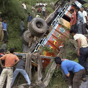 People look at the remains of a truck after it rolled down into a deep gorge in India, killing 38 partygoers (AP)