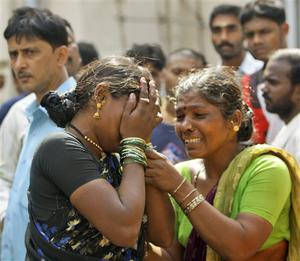 Sharda Janardhan Chitikar, left, is consoled by a relative as she grieves the death of her two children in a terrorist attack as she waits for their bodies outside St. Georges Hospital in Mumbai, India, Thursday, Nov. 27, 2008. Teams of gunmen stormed luxury hotels, a popular restaurant, a crowded train station and a Jewish group's headquarters, killing people, and holding Westerners hostage in coordinated attacks on the nation's commercial center that were blamed on Muslim militants. (AP Photo/Gurinder Osan)