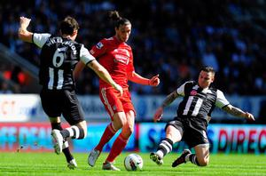 NEWCASTLE UPON TYNE, ENGLAND - APRIL 01:  Liverpool striker Andy Carroll is thwarted by Mike Williamson (l) and Danny Guthrie during the Barclays Premier League match between Newcastle United and Liverpool at Sports Direct Arena on April 1, 2012 in Newcastle upon Tyne, England.  (Photo by Stu Forster/Getty Images)