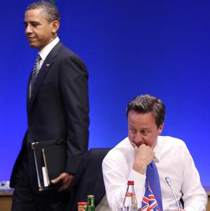 US president Barack Obama passes David Cameron during the internet session of the G8 summit