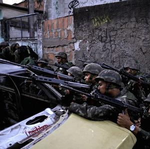 Soldiers aim their weapons during an operation against drug traffickers at the Complexo do Alemao slum in Rio de Janeiro (AP)