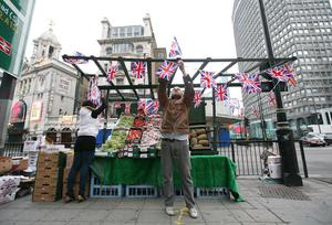 Dean Dwyer of Victoria Fruits, hangs Union flags from his fruit stall in Victoria, ahead of royal wedding at Westminster Abbey