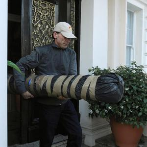 A man carries a package from the residence of the Iranian Charge D'Affaires in Knightsbridge, west London, as diplomats prepare to leave