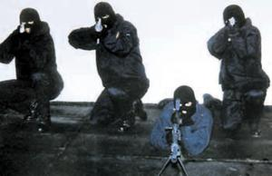 A masked and armed Mark Haddock (second left) poses in this picture of the notorious Mount Vernon unit of the UVF