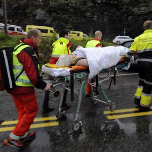 Medics and emergency workers escort an injured person from a camp site on the island of Utoya (AP)