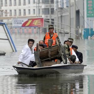Rescuers and disaster victims travel through a flooded street in the town of Zhouqu