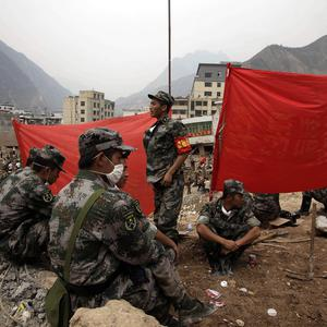 Chinese soldiers take a break from digging for victims of a mud slide that hit Gansu province (AP)