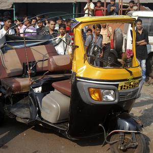 People look at a damaged rickshaw after a bus driver went on a rampage through the streets of Pune (AP)