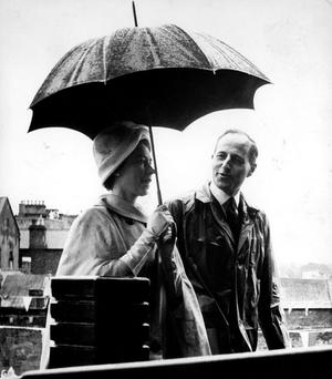 The Queen, Elizabeth 11. 1961 visit.Another summer shower as Captain Terence O'Neill, then Minister of Finance. accompanies. August 1961