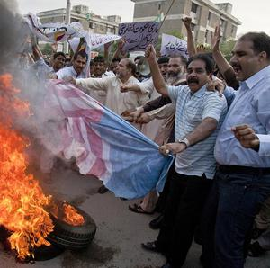 Pakistani traders burn a US flag as part of widespread anger across the Muslim world about a film ridiculing the prophet Muhammad (AP)