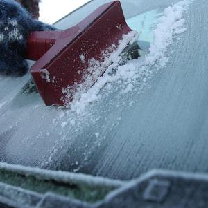 A woman became trapped underneath her car while attempting to defrost it, police said