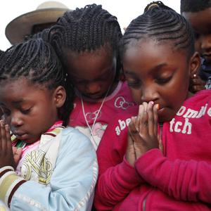 Children in Atlanta pray during a moment of silence for the 44th anniversary of the assassination of Dr Martin Luther King (AP)
