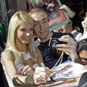 Gwyneth Paltrow signs an autograph and poses for a photo following dedication ceremonies for her star on the Hollywood Walk of Fame