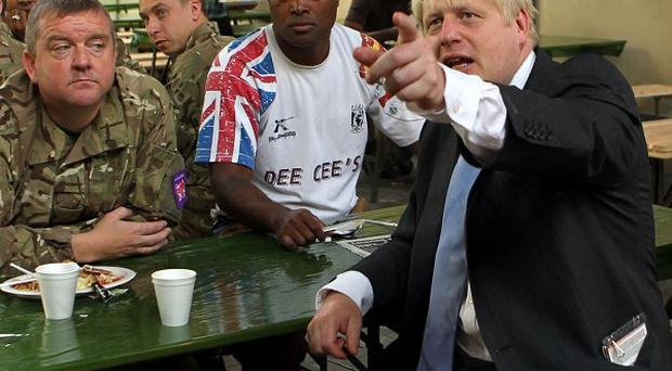 Boris Johnson watches the Olympics during a visit to meet members of the armed forces in Tobacco Dock