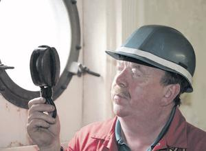 Robert Mahood of Harland and Wolff holds a rigging block, an old tool still used in the shipyard, on the Nomadic