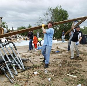 Volunteers carry a piece of debris to a rubbish pile at a home destroyed by a tornado in Piedmont (AP)