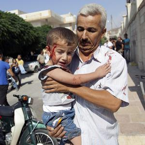 A Syrian man carries an injured child to a field hospital after an air strike hit homes in the town of Azaz on the outskirts of Aleppo (AP)