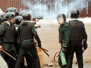 An RUC officer fires plastic bullets at rioting nationalists on the Garvaghy Road